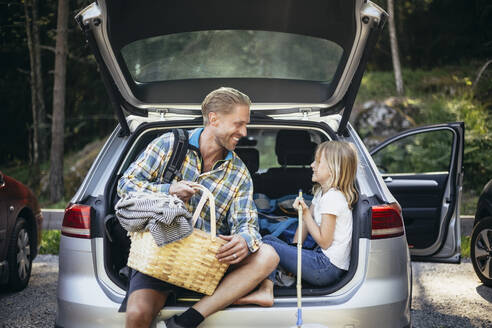 Smiling father with picnic basket talking to daughter while sitting in car trunk - MASF20205