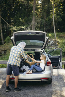 Side view of daughter covering father's face with fishing net while sitting in car trunk - MASF20208