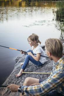 Smiling daughter enjoying fishing with father at lake - MASF20217