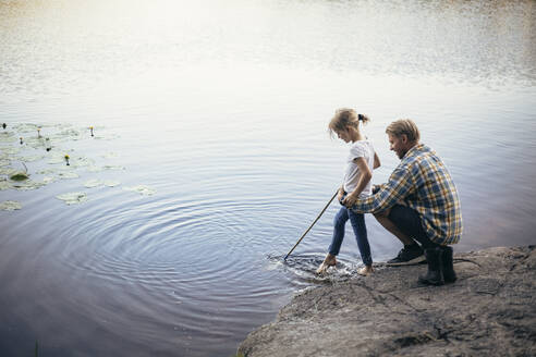 Father holding daughter during fishing by lake - MASF20223