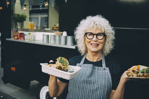 Portrait of senior owner with street food standing against commercial land vehicle in city - MASF20241