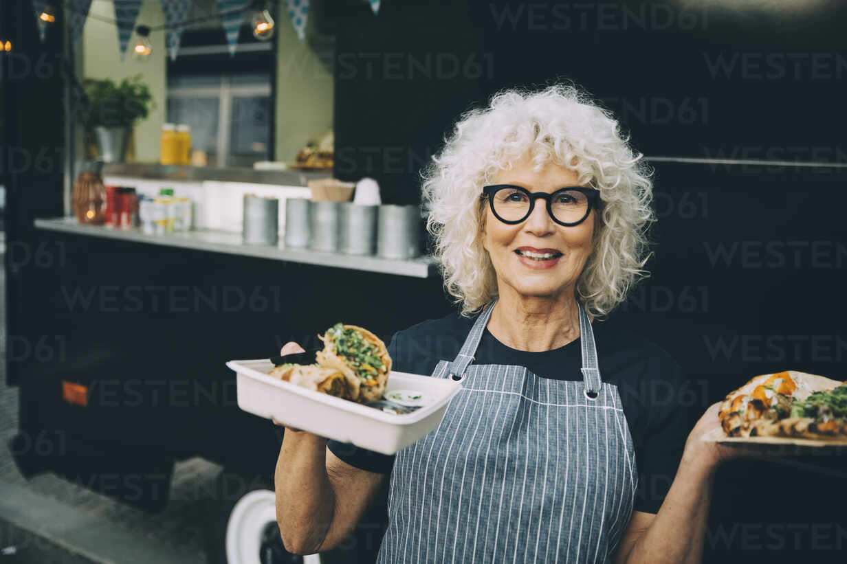 Portrait of senior owner with street food standing against commercial land vehicle in city - MASF20241 - Maskot/Westend61