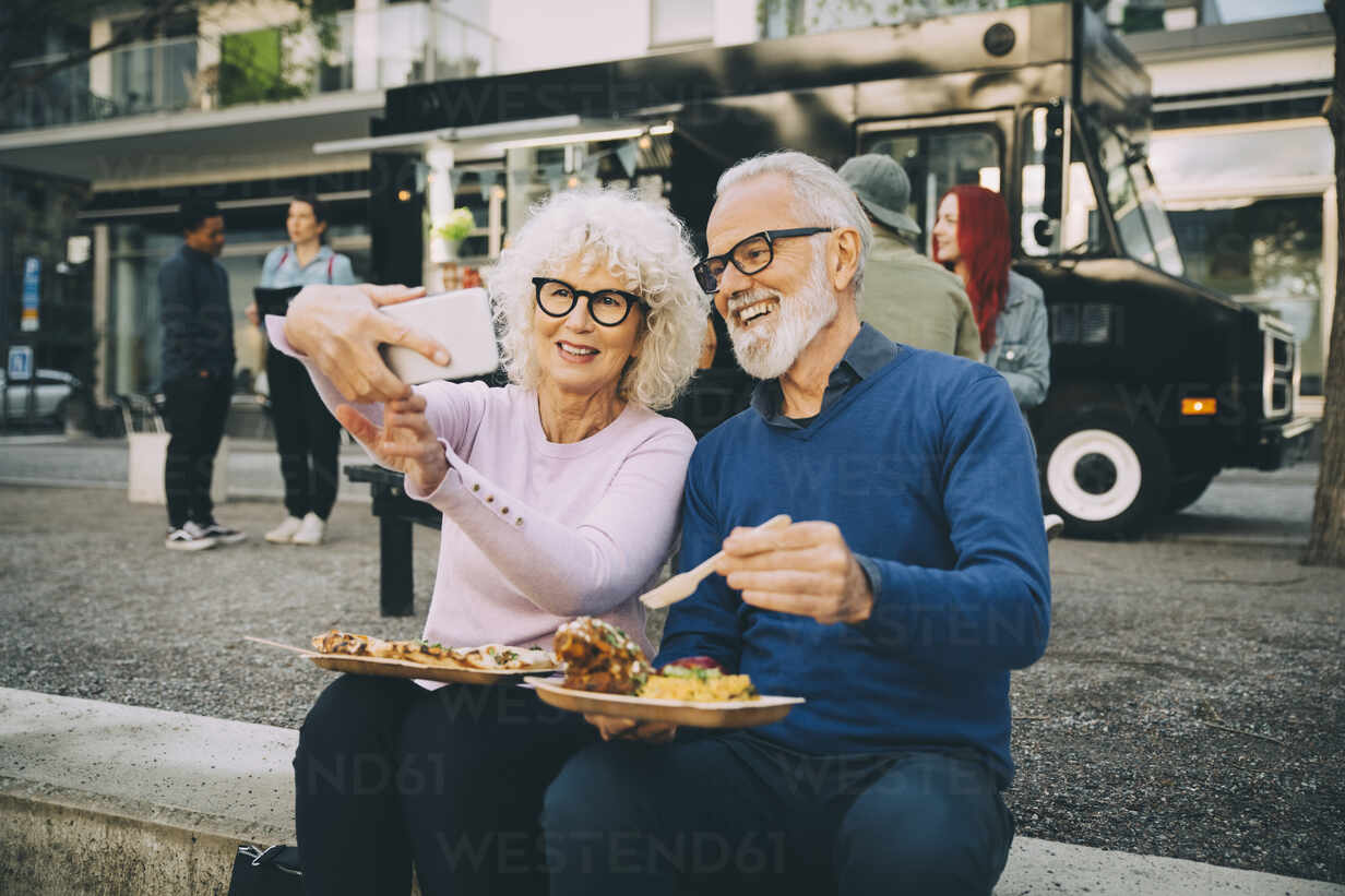 Smiling senior woman taking selfie with man eating meal against food truck in city - MASF20247 - Maskot/Westend61