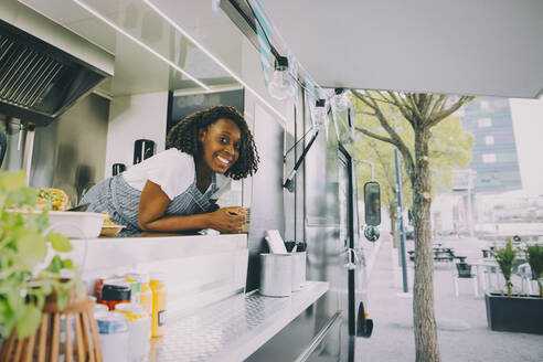 Portrait of smiling female owner standing in food truck - MASF20271