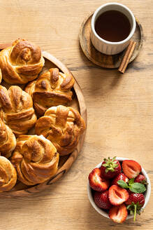 Stack of tasty cinnamon rolls placed on wooden table with cup of coffee in kitchen - ADSF16971