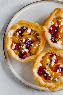 Top view of yummy tarts made of filo dough and filled with sliced fruits served with cup of aromatic coffee with milk - ADSF16974