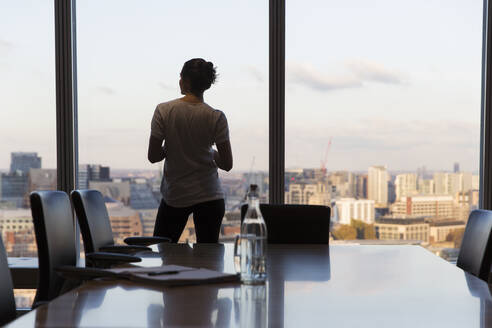 Thoughtful businesswoman looking out highrise office window - CAIF29721