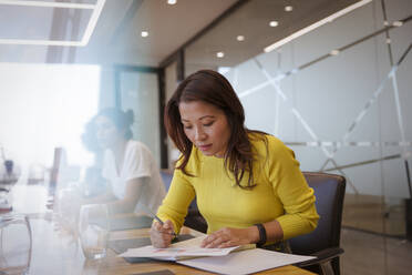 Businesswoman with paperwork in conference room meeting - CAIF29757