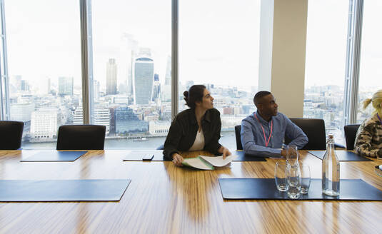 Business people listening in highrise conference room meeting - CAIF29784
