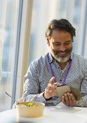 Smiling businessman using smart phone at lunch - CAIF29790