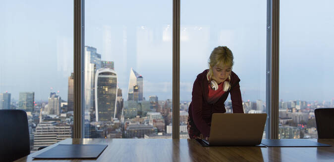 Businesswoman using laptop in highrise office, London, UK - CAIF29793