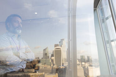 Thoughtful businessman looking out highrise office window, London, UK - CAIF29799