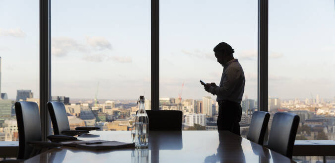 Businessman using smart phone at highrise office window, London, UK - CAIF29805