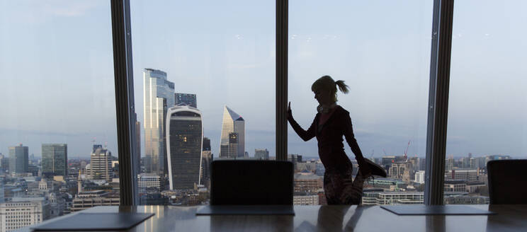 Businesswoman stretching at highrise office window, London, UK - CAIF29808