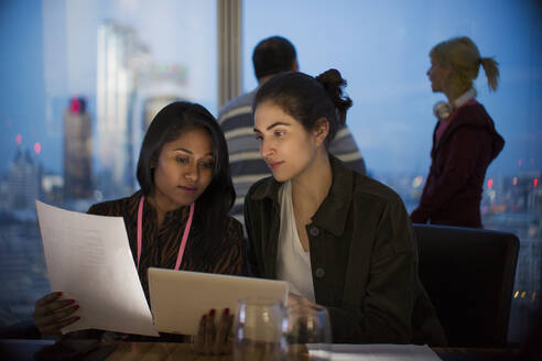 Businesswomen with digital tablet working late in office - CAIF29811