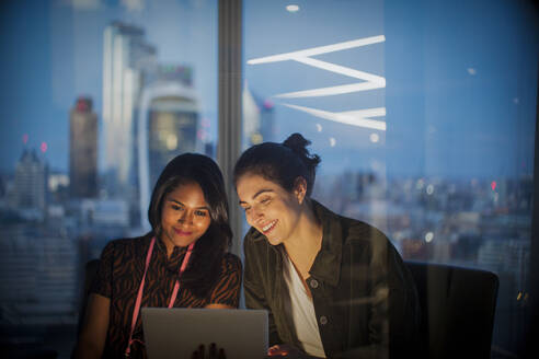 Businesswomen with digital tablet working late in office, London, UK - CAIF29814
