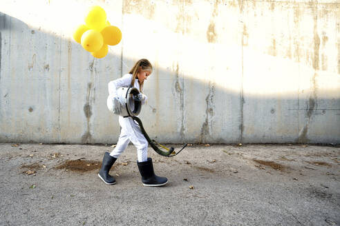 Little girl walking with space helmet and holding balloon on street during sunny day - GGGF00002