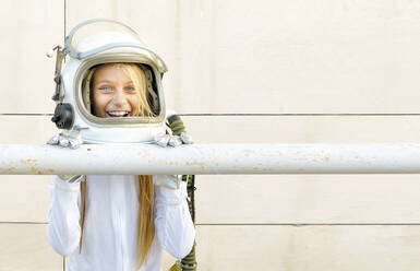 Girl wearing space suit leaning on railing against wall during sunny day - GGGF00005