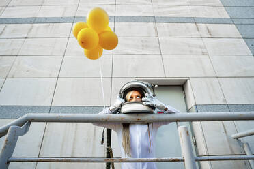 Girl leaning on railing while holding yellow balloon - GGGF00008
