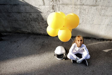 High angle view of girl holding yellow balloon sitting against wall during sunny day - GGGF00011