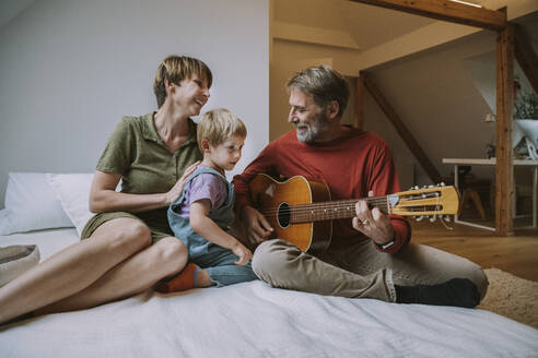 Father playing guitar while mother and son sitting on bed in bedroom at home - MFF06622