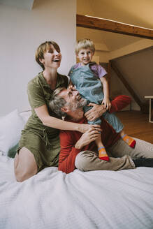 Mother and father embracing son while sitting on bed at home - MFF06628