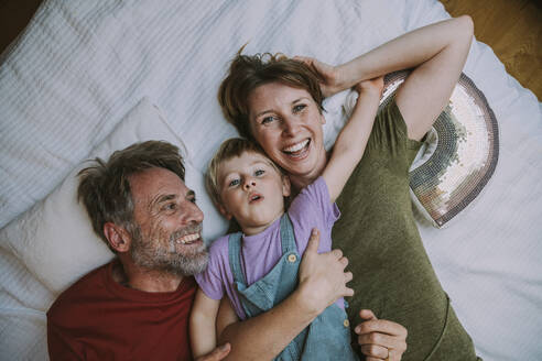 Smiling mother, father and son lying on bed at home - MFF06631