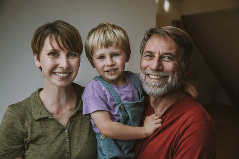 Smiling family standing at home - MFF06640