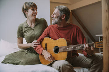 Mature man playing guitar while woman looking at him sitting on bed in bedroom - MFF06643