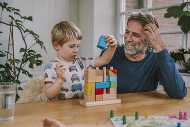 Father watching son playing with puzzle while sitting at home - MFF06652