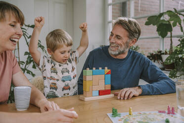 Mother and father playing with cheerful son toy block puzzle at home - MFF06655