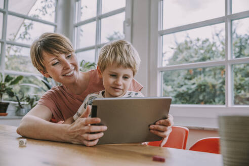 Mother holding digital tablet with son while sitting at home - MFF06664