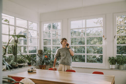Mid adult woman talking on smart phone looking away while standing at home - MFF06685