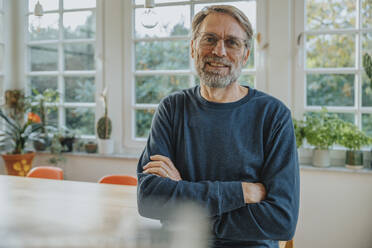 Happy mature man with arms crossed standing at home - MFF06688