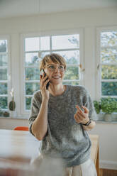 Smiling woman talking on smart phone looking away while standing at home - MFF06691