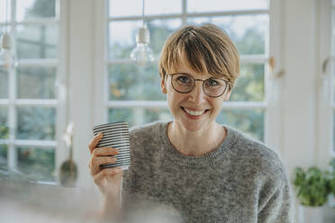 Smiling mid adult woman holding tea cup while standing at home - MFF06694