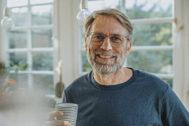 Smiling mature man with tea cup standing at home - MFF06697