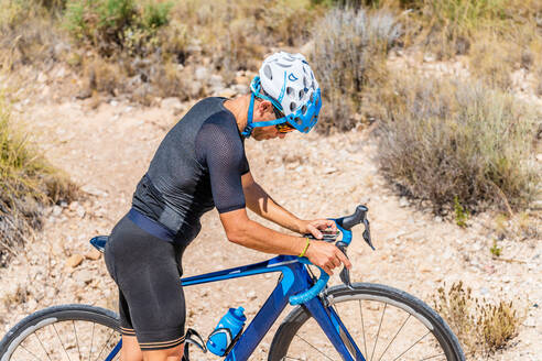Side view of sporty male bicyclist in activewear and helmet navigating with electronic equipment while riding bike in mountainous area - ADSF17078