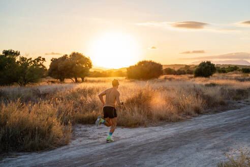 Back view of unrecognizable active male athlete with strong body running along rural road and checking time on wristwatch during intense training in summer sunset - ADSF17093