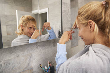Mature woman looking in mirror cutting her own hair at home - PMF01420