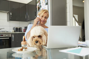 Mature woman talking on smart phone sitting with dog in kitchen at home - PMF01426