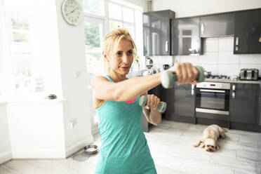 Mature sportswoman exercising with dumbbells at home - PMF01435