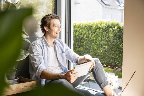 Smiling man holding digital tablet looking away while sitting at home - UUF21858