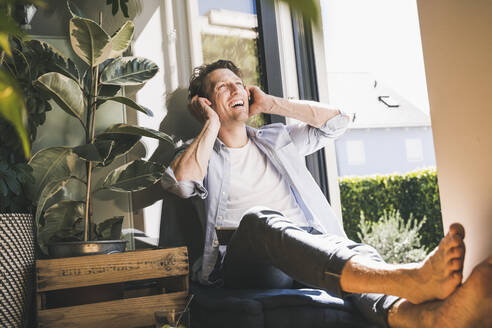 Man laughing while listening music through headphone sitting at home - UUF21873