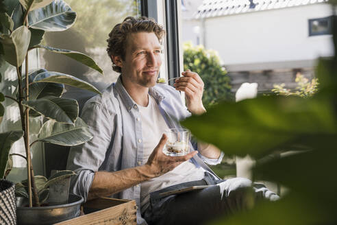 Mid adult man smiling while eating food sitting at home - UUF21876