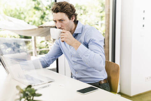 Man working on laptop while drinking coffee sitting in office - UUF21897