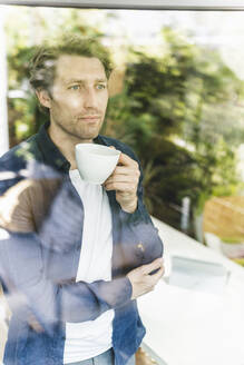 Mid adult man looking through window while drinking coffee standing at home - UUF21906