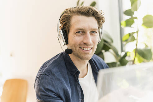 Smiling mid adult man wearing headphone sitting at home - UUF21912