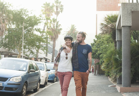 Couple walking with arm around on street - AJOF00392