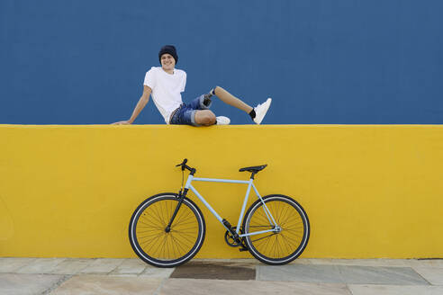 Young male with disability sitting near bike - CAVF89805